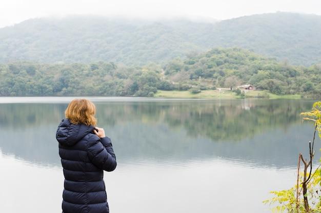 Vrouw aan het meer genieten van het uitzicht