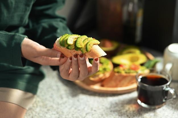 Vrouw aan het ontbijt in de keuken.