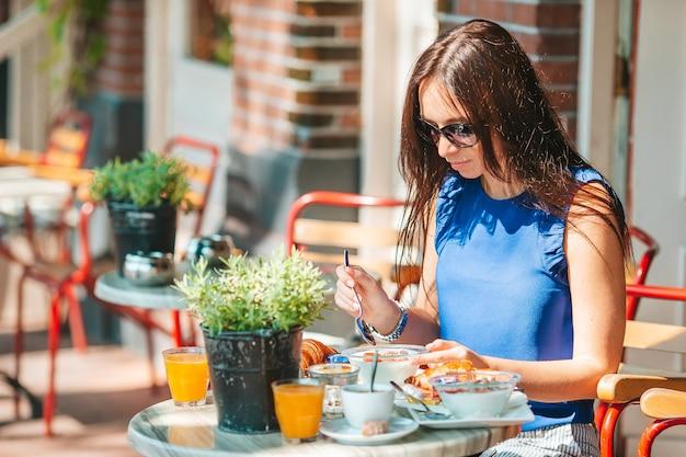 Vrouw aan het ontbijten in de buitenlucht