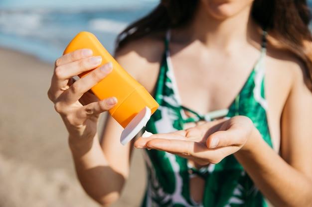 Vrouw aan het strand met zonnebrandcrème