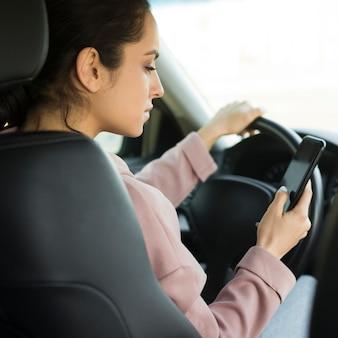 Vrouw aan het stuur met behulp van haar telefoon