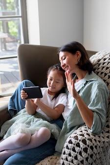 Vrouw aan het videobellen met haar man naast hun dochter