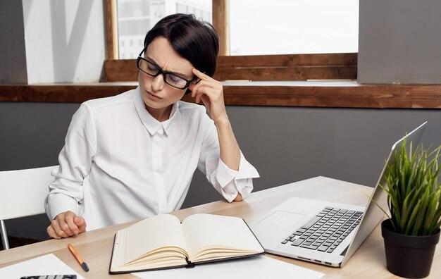 Vrouw aan het werk achter laptop in kantoor zakelijke financiën en kladblok op tafel.