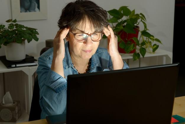 Vrouw aan het werk met computer die aan pijnlijke hoofdpijn lijdt