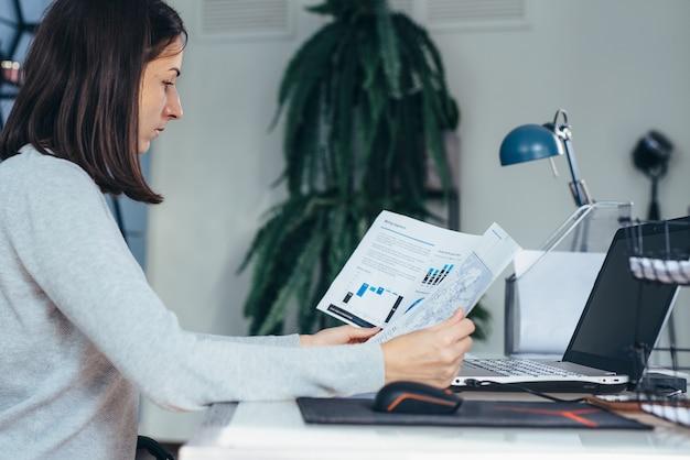 Vrouw aan het werk op haar bureau met documenten en laptop.
