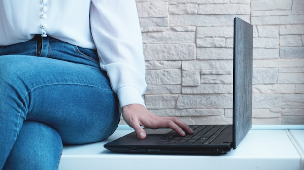 Vrouw aan het werk op kantoor aan huis hand op toetsenbord close-up op bakstenen muur