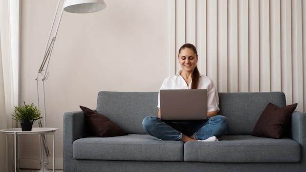 Vrouw aan het werk op laptop vanuit huis of student studeert vanuit huis of freelancer. moderne zakenvrouw in een wit overhemd en spijkerbroek.