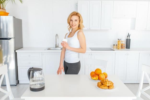 Vrouw aan tafel, fruitontbijt in de keuken