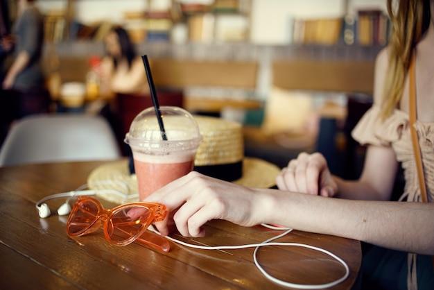 Vrouw aan tafel in café vakantie koptelefoon hoed levensstijl interieur.