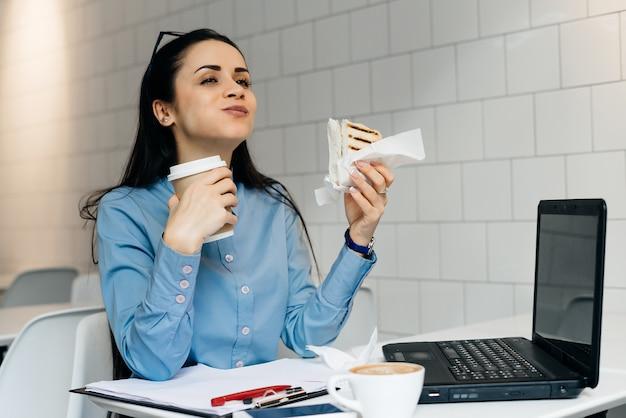 Vrouw aan tafel koffie drinken en sandwich eten