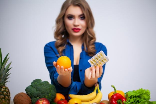 Vrouw aan tafel met sinaasappel en pillen op groenten en fruit