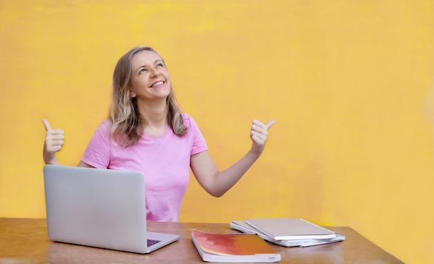 Vrouw aan tafel zitten met laptop en duimen opdagen op gele achtergrond