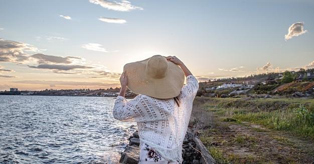 Vrouw aan zee bij zonsondergang achteraanzicht. gekleed in een lange rok en hoed.