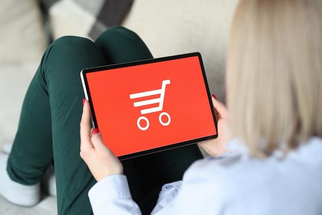 Vrouw aanbrengen op de bank en tablet in haar handen te houden. online winkelconcept