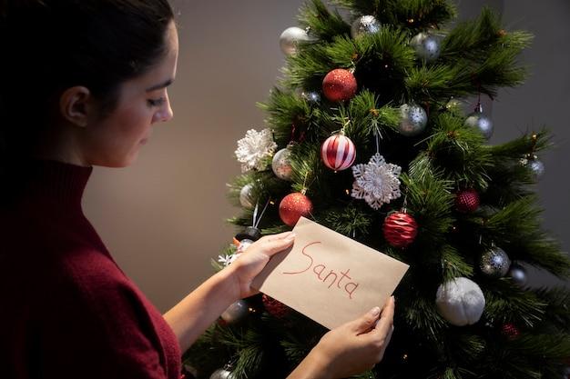 Vrouw aanbrengend kerstboom brief voor de kerstman