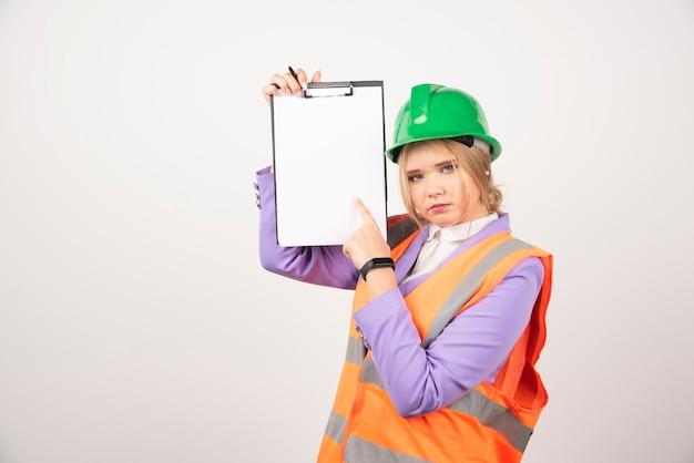 Vrouw aannemer met groene helm klembord op wit te houden.