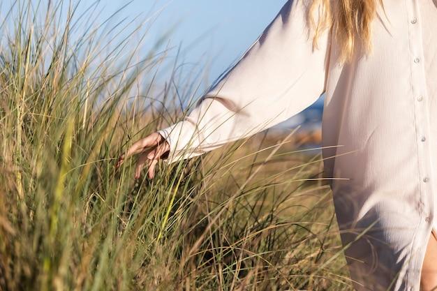Vrouw aanraken van gras close-up