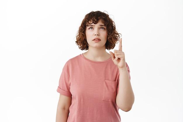 Vrouw aarzelend wenkbrauwen optrekkend, wijzend en opkijkend met een twijfelachtig, ondervraagd gezicht, kopieerruimte bovenop lezend, staand in t-shirt op wit.