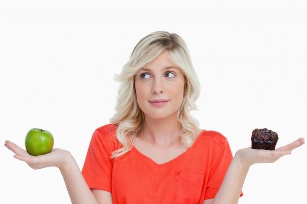Vrouw aarzelt tussen een chocolademuffin en een groene appel