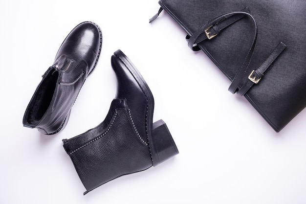 Vrouw accessoire. zwarte stijlvolle laarzen, zwarte luxe lederen tas. bovenaanzicht plat leggen.