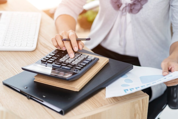 Vrouw accountant bezig met rekeningen in bedrijfsanalyse met grafieken en document financiële gegevensrapport met laptopcomputer op kantoor, bedrijfsconcept.