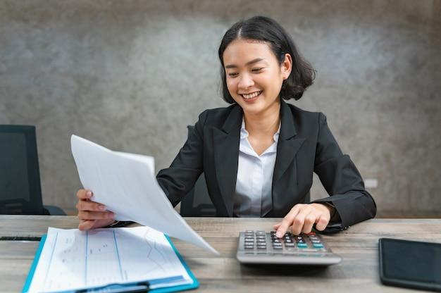 Vrouw accountant calculator gebruiken voor het berekenen van financiële rapport in kantoor