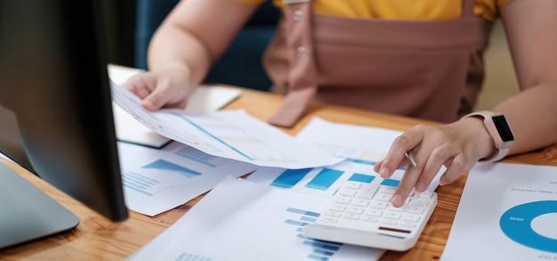 Vrouw accountant die werkcontrole maakt en de financiële jaarlijkse financiële verslagbalans van de uitgaven berekent, financiën doet en aantekeningen maakt op papier die de inspectie controleert.