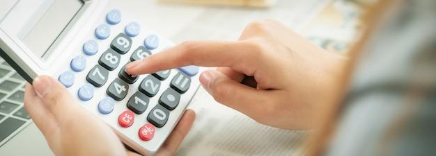 Vrouw accountant of bankbediende maakt gebruik van calculator.