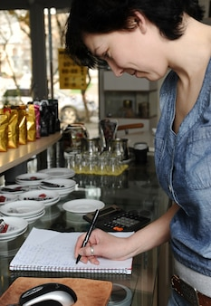 Vrouw achter de toonbank van een café is het maken van aantekeningen in een notitieblok.