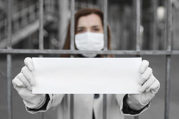 Vrouw achter de tralies in isolatie houdt een leeg bordje zonder inscriptie