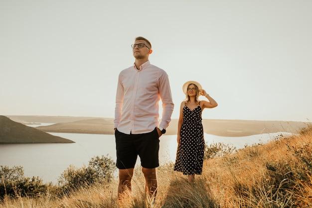 Vrouw achter man in stralen van de ondergaande zon in de zomer in de buurt van meer