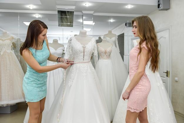 Vrouw adviseur helpt bruid bij het kiezen van bruidsjurk