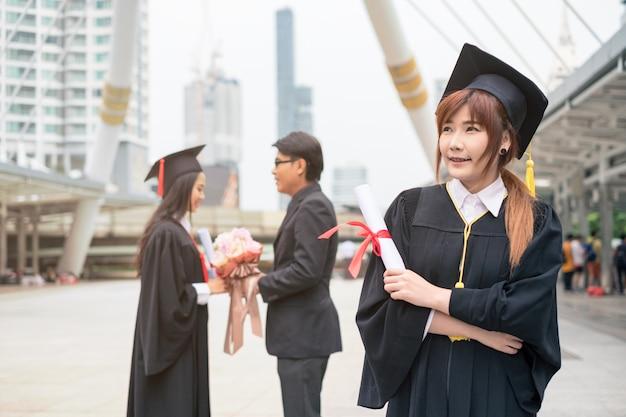 Vrouw afgestudeerd bachelor's degree met diploma met paar felicitatie
