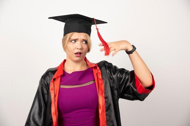 Vrouw afgestudeerde student in toga opzij op zoek op wit.