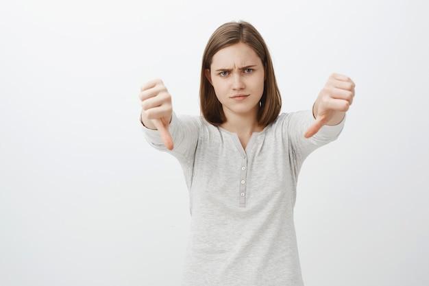 Vrouw afkeurende vriendenproject. een portret van een niet onder de indruk en ontevreden schattig meisje met een kort bruin kapsel, fronsend en met tuitende lippen van afkeer, duimen naar beneden laten zien en eigen negatieve mening uiten