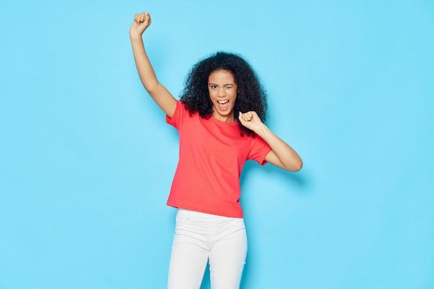 Vrouw african american in een t-shirt in de studio op blauw