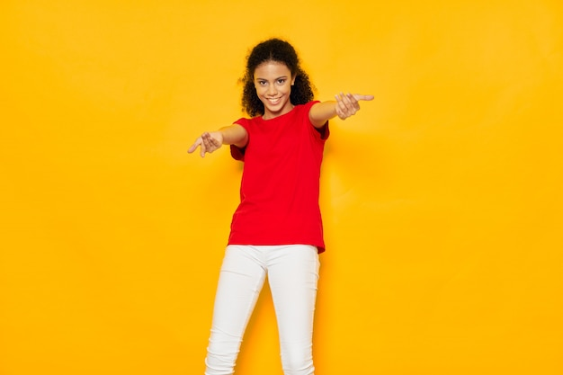 Vrouw african american in een t-shirt in de studio op een gekleurde oppervlak poseren