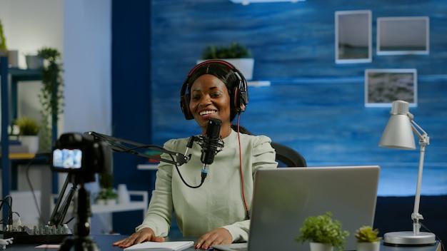 Vrouw afrikaanse vlogger neemt op naar camera-tutorial over levensstijl in thuispodcaststudio tijdens livestreaming. on-air online productie internet uitzending show host streaming live content voor social