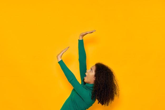 Vrouw afro-amerikaanse in een t-shirt ruimte op een gekleurde ruimte poseren