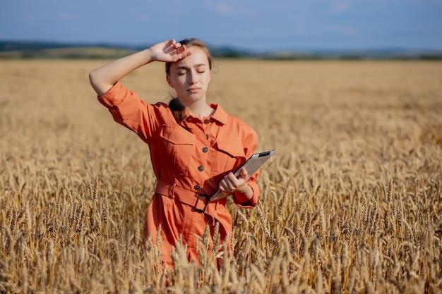 Vrouw agronoom met tabletcomputer op het gebied van tarwe kwaliteitscontrole