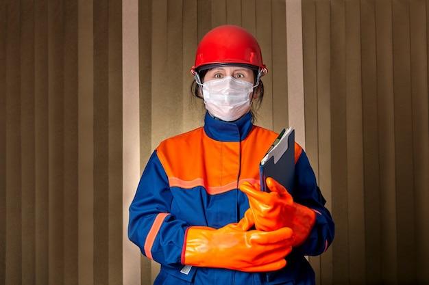 Vrouw als elektrotechnisch ingenieur gebruikt beschermende kleding en gezichtsmasker om zich te beschermen tegen arbeidsgerelateerde verwondingen en tegen coronavirus-infectie covid-19 pandemie.