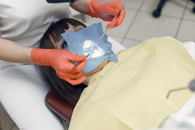 Vrouw als tandartsstoel. het meisje legt een vulling op de tand. schoonheid behandelt haar tanden