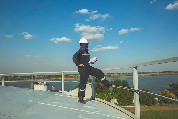 Vrouw als werknemer visuele inspectie opslagtank olie top dak oil