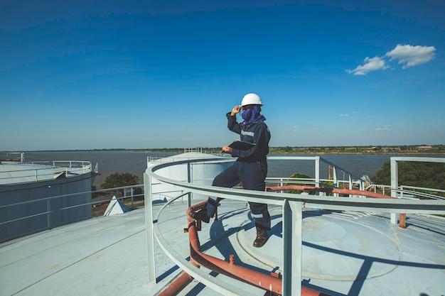 Vrouw als werknemer visuele inspectie opslagtank olie top dak