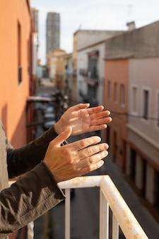 Vrouw applaudisseert op een balkon van spanje groet voor werken van artsen, verpleegkundigen, beleid tijdens de coronavirusepidemie