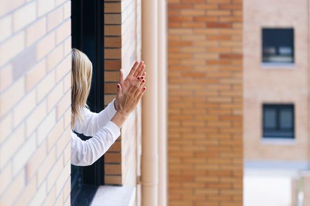 Vrouw applaudisseert vanaf haar balkon om diegenen te bestrijden die het coronavirus bestrijden
