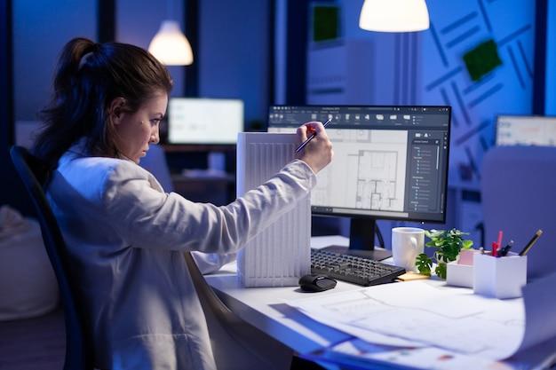 Vrouw architect analyseert en matcht blauwdrukken voor nieuwbouwproject