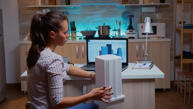 Vrouw architect matching prototype met plannen van laptop thuiswerken overuren. ontwerper die cad-software gebruikt om een 3d-concept te ontwerpen van gebouwen die 's avonds laat worden gemaakt en bestudeerd