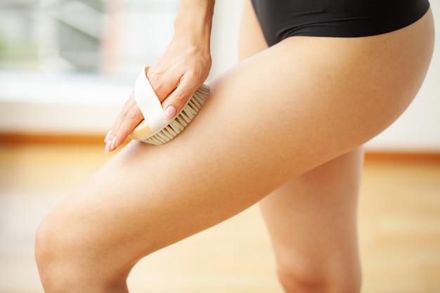Vrouw arm met droge borstel boven haar been, cellulitis behandeling en droog borstelen.