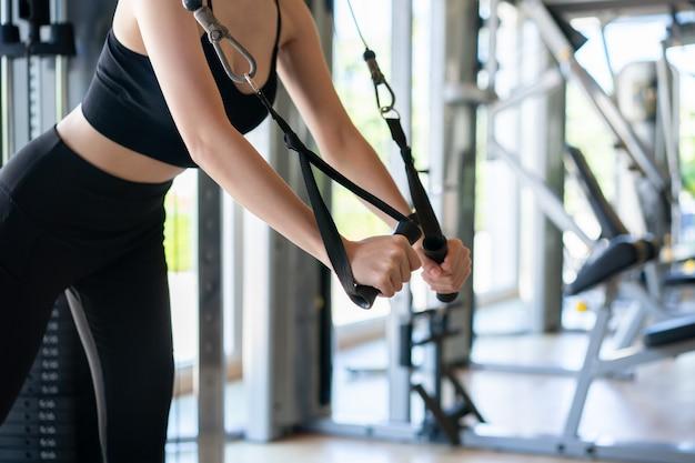 Vrouw armen kabel vliegen oefening in sportschool doen.